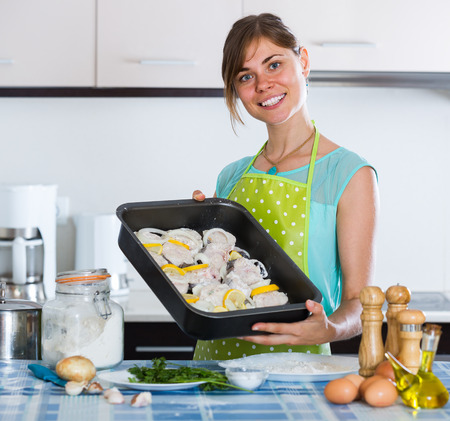 25 35: Happy russian housewife putting pieces of white fish in tray