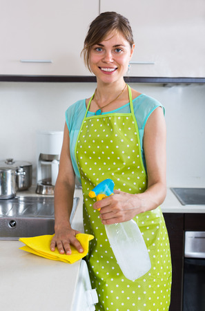 cleanup: Young female doing professional clean-up in home kitchen Stock Photo