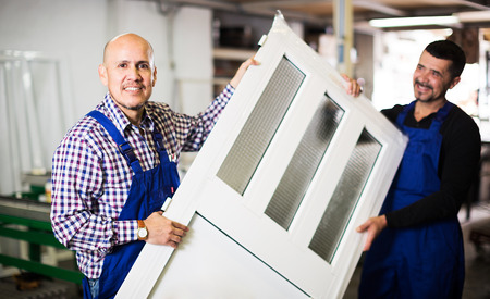 enginery: labours with finished PVC profiles and windows at factory Stock Photo