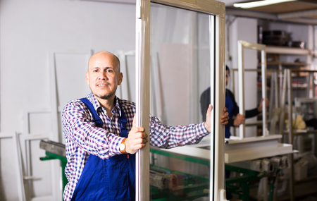 glasswear: Professional workmen produce PVC profiles and windows at factory
