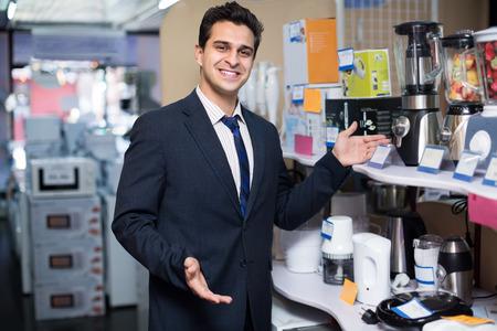 Vendeur souriant positif travaillant à la section des petits appareils ménagers
