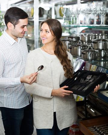 25 35: young couple choosing at cutlery at shop
