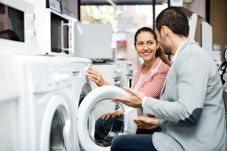 lavadora con ropa: Beautiful family couple buying new clothes washer in supermarket. Focus on the woman