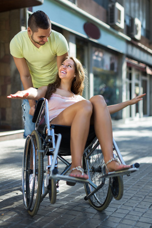invalidity: Young husband taking smiling young spouse on wheelchair in playful mood outside