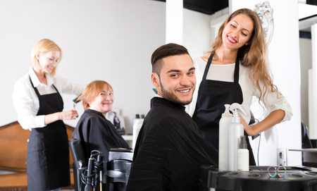 upsweep: Portrait of a happy man with a new haircut in a hair styling salon