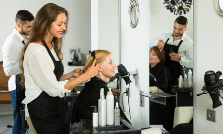 haircutter: Stylists works with woman hair in salon