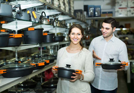 25 35: smiling european couple chooses pans in shop cookware