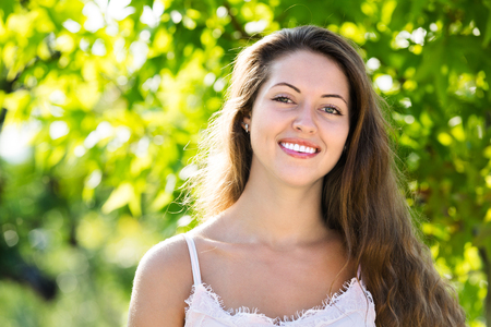 Attractive smiling young female in summer park