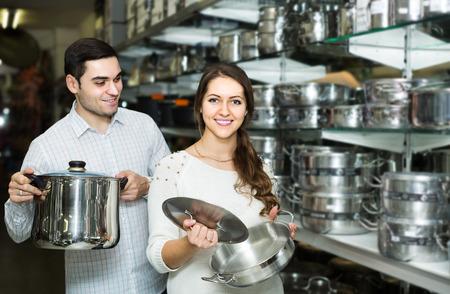 utensilios de cocina: Pares europeos joven elige sartenes en la tienda de utensilios de cocina