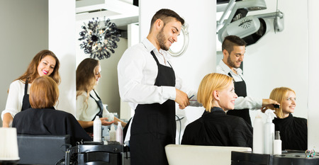 Hair stylist working on haircut for beautiful woman Stock Photo