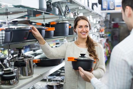 utensilios de cocina: Smiling hombre y mujer compra en la tienda de utensilios de cocina sartenes Foto de archivo