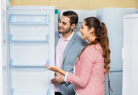 domestic appliances: Satisfied young customers looking at large fridges in domestic appliances section
