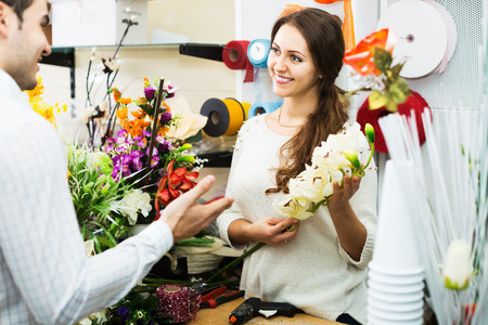 flower seller: Woman seller helping man to pick floral bouquet at flower shop