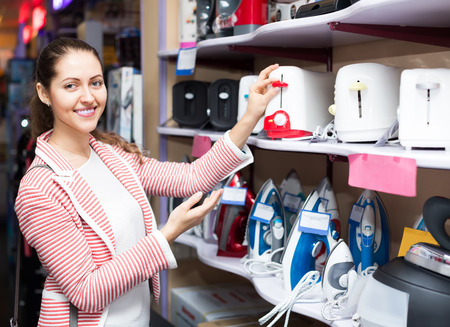 Young brunette choosing pop-up toaster in hypermarket and smiling