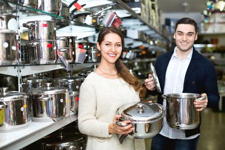 cookware: Feliz pareja sonriente en la sección de utensilios de cocina en el hipermercado