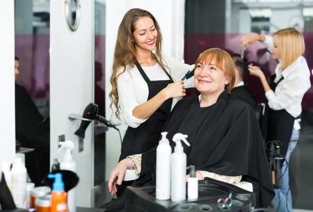 hairdressing salon: Senior mature woman cutting her hair at the hairdressing salon