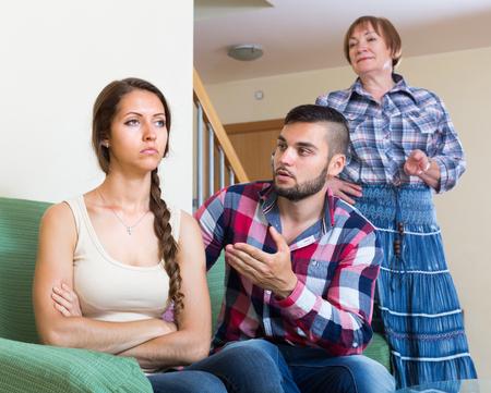 femme triste: Jeune couple mari� ayant conflit avec sa m�re �g�e � la maison. mise au point s�lective Banque d'images
