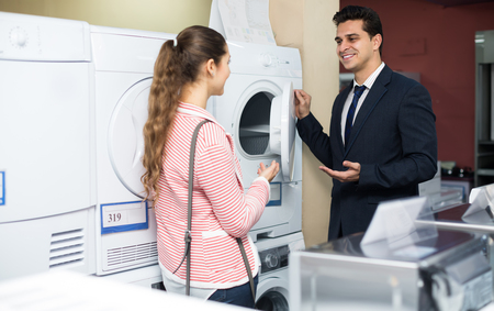 domestic appliances: Smiling customers choosing laundry machine in domestic appliances section
