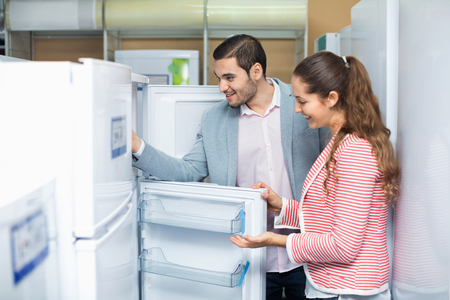 Satisfied smiling couple looking at large fridges in domestic appliances section Banco de Imagens