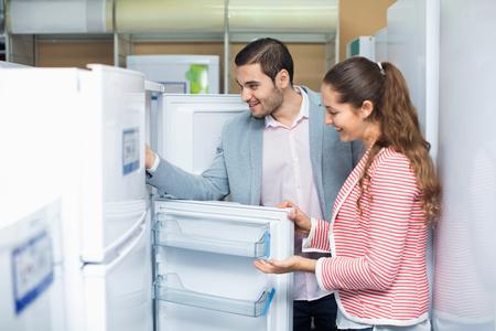 Tevreden lachend paar op zoek naar grote koelkasten in huishoudelijke apparaten sectie Stockfoto