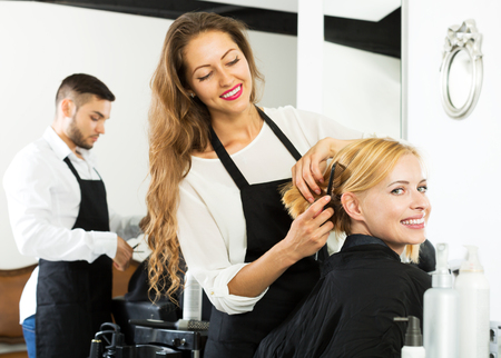 Hair stylist working on haircut for cheerful girl. Focus on the client