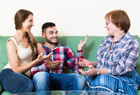mother in law: smiling  couple sitting in living room and talking with mother Stock Photo