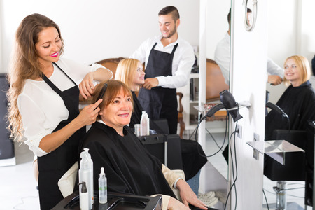 25 35: Smiling senior mature woman cutting hair in the hairdressing salon