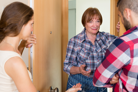 neighbour: Young family having conflict with a elderly female neighbour at the door Stock Photo