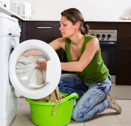 stereotypical: Home laundry. Young housewife using washing machine at home