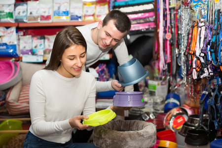 18 20: Happy young boyfriend helping smiling girl to choose bowl in pet store. Focus on girl Stock Photo