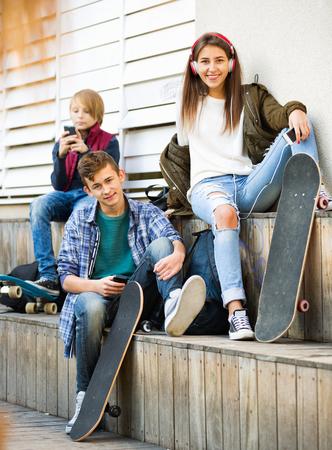 escucha activa: adolescentes activos felices jugando en smarthphones y escuchar música