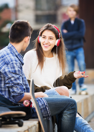 16s: Envy male teen standing aside of girlfriend talking with boy Stock Photo