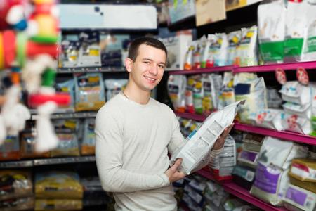 veterinaria: Retrato de hombre viendo productos de la dieta y la sonrisa en la tienda de mascotas