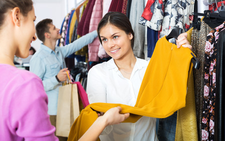 Young female assistant serving customer asking in clothing boutique
