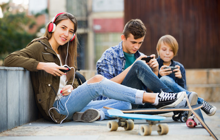 teens playing: Young cheerful teens playing on smarthphones and listening to music Stock Photo