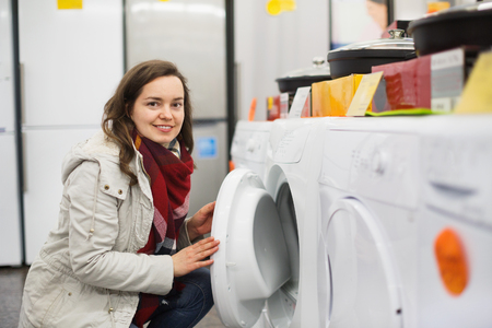 domestic appliances: Positive female customer looking at dryers in domestic appliances section