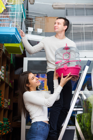 19's: Portrait of young couple 19s purchasing bird cage in petshop