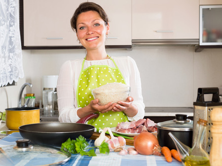 25 35: Adult woman preparing rice with meat at domestic kitchen