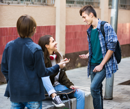 blabbing: Three positive smiling teenagers hanging out outdoors and discussing something