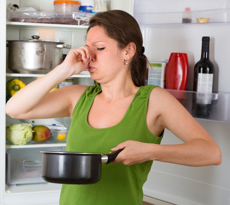 frowy: Girl holding foul food near refrigerator at home kitchen