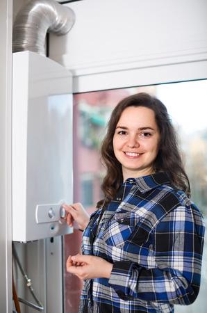 Charming american adult girl in shirt near boiler control panel Stock fotó