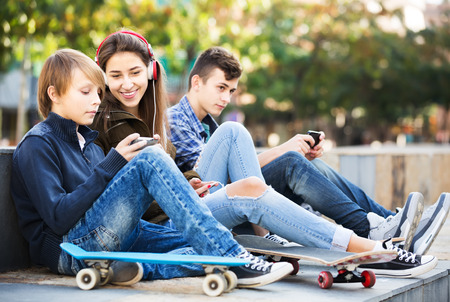 16s: Teenage males and girl relaxing with smartphones in the city. Focus on girl