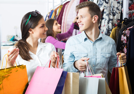 clothing store: Happy young friends together carrying bags with purchases in boutique