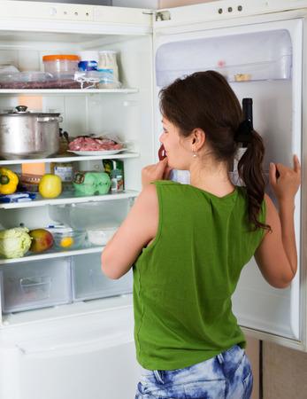 refrigerador: La mujer joven que busca algo en la nevera en la cocina de su casa