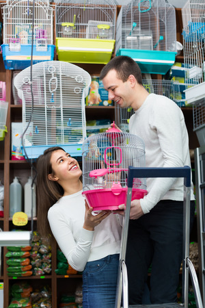 petshop: Ordinary young couple buying cage for bird in shop