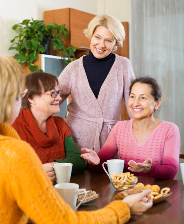 talkative: Smiling female pensioners drinking coffee and talking