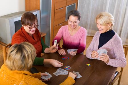 55 60: Positive happy senior female friends staking money during bridge Stock Photo