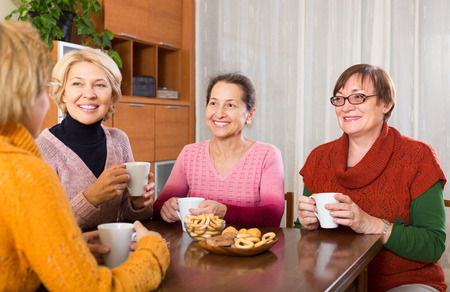 talkative: Smiling female pensioners drinking coffee at home and talking