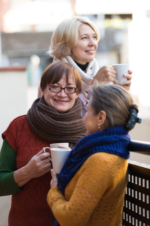 55 60: Two mature women drinking a tea on balcony and smiling