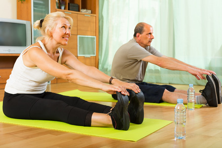 remedial: Happy senior spouses warming up muscles before exercising at home